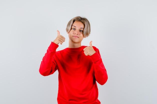 Молодой мальчик-подросток в красном свитере показывает двойные пальцы вверх