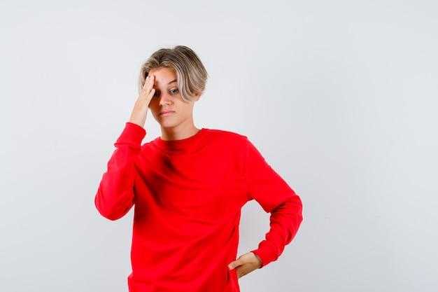 頭に手を置いて、見下ろし、思慮深く、正面図で赤いセーターを着た若い十代の少年。