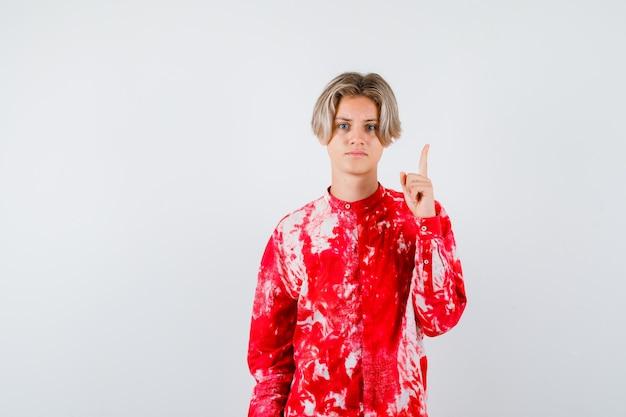 Молодой мальчик-подросток в рубашке, указывая вверх и глядя сердиться, вид спереди.