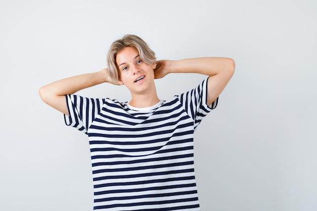 頭の後ろに手とリラックスした、正面図の縞模様のtシャツを着た若い10代の少年。