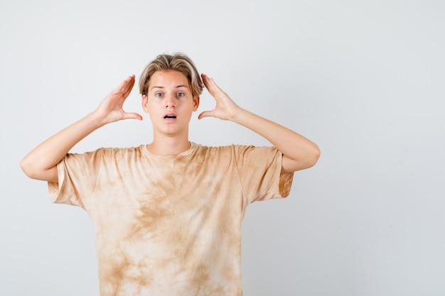 手で頭を留める準備をしていて困惑しているように見えるtシャツの若い10代の少年、正面図。