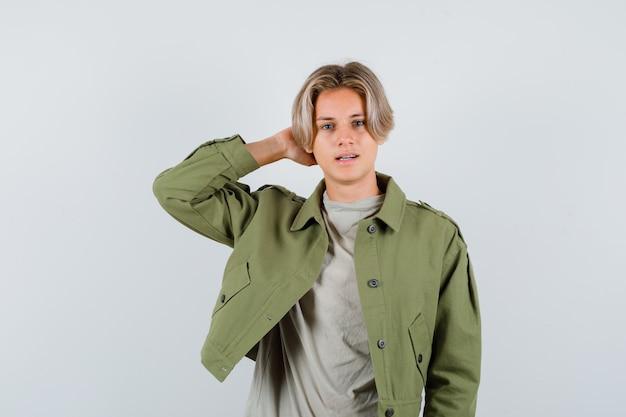 Tシャツを着た若い十代の少年、頭の後ろに手を保ち、混乱しているように見えるジャケット、正面図。