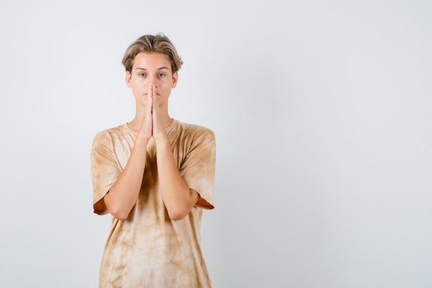 祈りのジェスチャーで手を保ち、希望に満ちた、正面図を探しているtシャツの若い10代の少年。