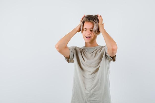 頭に手を置いて、ダウンキャスト、正面図を見てtシャツを着た若い10代の少年。