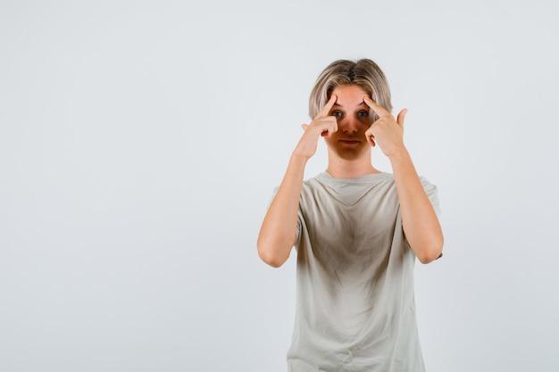 Молодой мальчик-подросток в футболке, указывая на его лоб и выглядящий умным, вид спереди.