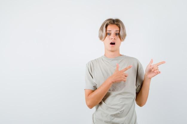 右向きで驚いた様子のtシャツを着た若い10代の少年、正面図。