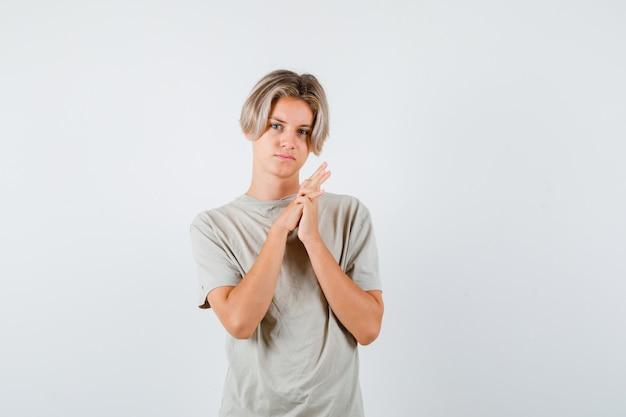 티셔츠를 입은 어린 10대 소년이 손을 함께 누르고 사려깊은 전면 전망을 보고 있습니다.