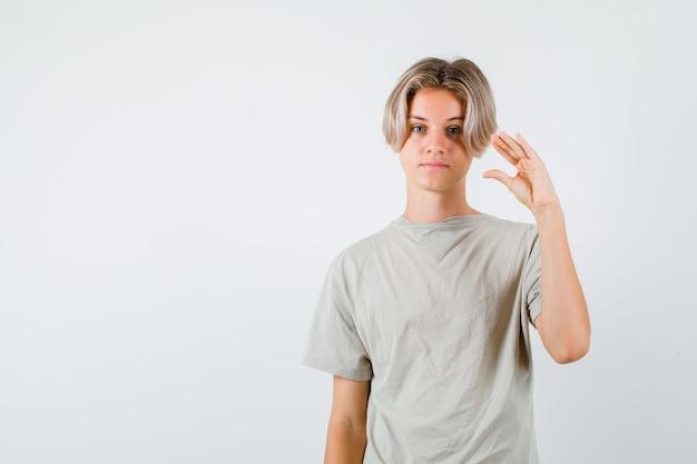 Молодой мальчик-подросток в футболке показывает жест бла-бла-бла и выглядит саркастичным, вид спереди.