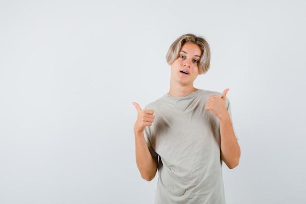 Tシャツを着た若い10代の少年は、二重の親指を上に表示し、満足そうに見える、正面図。