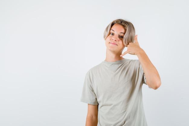 Молодой мальчик-подросток в футболке показывает жест телефона и выглядит веселым, вид спереди.