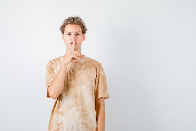 Молодой мальчик-подросток в футболке показывает жест молчания и выглядит разумно, вид спереди.