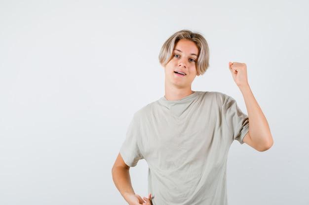 Молодой мальчик-подросток в футболке показывает жест победителя и выглядит удачливым, вид спереди.