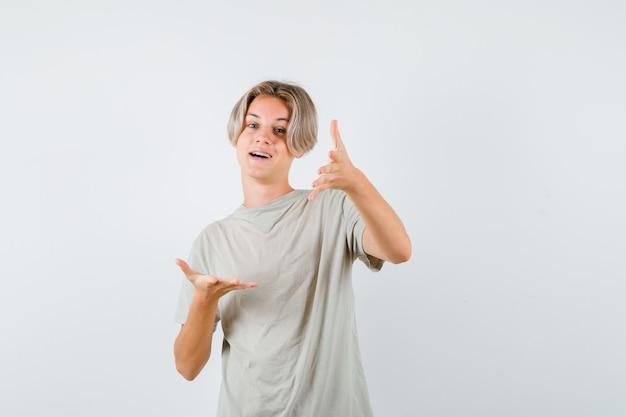 티셔츠를 입은 어린 10대 소년이 카메라를 향해 손을 뻗고 행복해 보입니다.