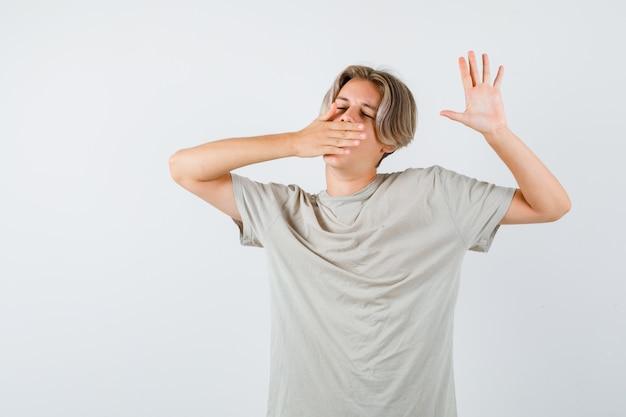 あくびをして上半身を伸ばし、眠そうなtシャツを着た10代の少年