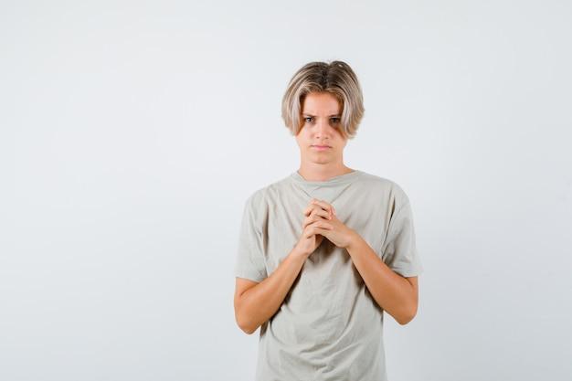 Giovane ragazzo adolescente che tiene le mani giunte sul petto in maglietta e sembra sconvolto. vista frontale.