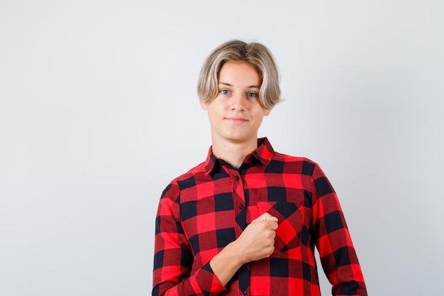 체크 셔츠를 입은 채 가슴에 주먹을 쥔 어린 십대 소년은 자신감 있고 앞모습을 보고 있습니다.