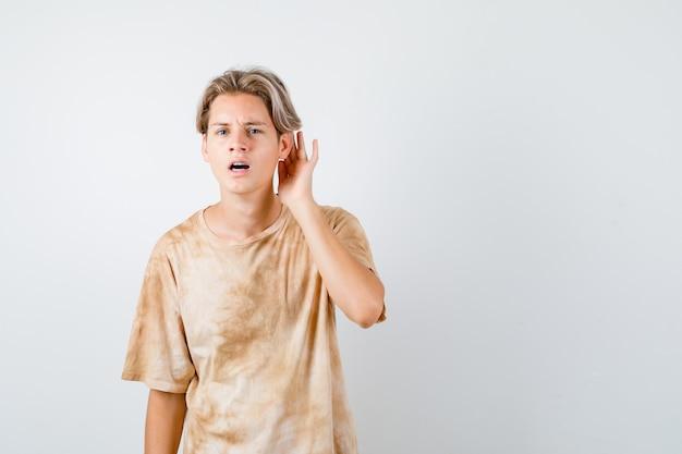 어린 십대 소년이 티셔츠를 입고 귀 뒤에 손을 잡고 어리둥절한 표정을 짓고 있습니다.