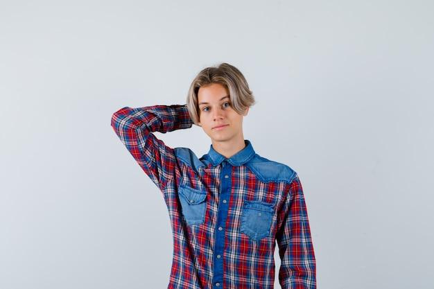 チェックのシャツを着て頭の後ろに手を保ち、自信を持って見える若い十代の少年。正面図。