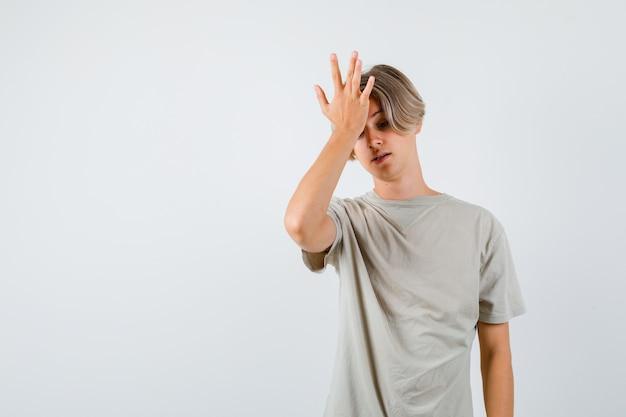 Tシャツで額に手を置いて、忘れられている、正面図を探している若い10代の少年。