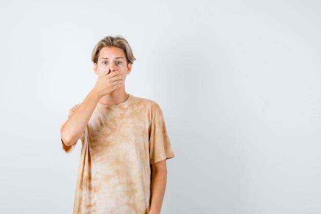 若い十代の少年は、tシャツを着て口に手を保ち、興奮しているように見えます。正面図。
