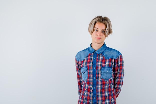 Giovane ragazzo adolescente che tiene le mani dietro la schiena in camicia a quadri e sembra sicuro. vista frontale.