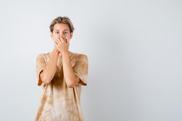 Giovane ragazzo adolescente che tiene le mani sulla bocca in maglietta e sembra ansioso, vista frontale.