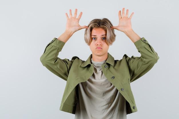 Молодой мальчик-подросток держит руки возле головы как уши в футболке, куртке и выглядит разочарованным. передний план.