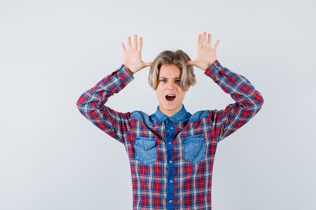 Young teen boy keeping hands near head as ears while screaming in checked shirt and looking crazy , front view.