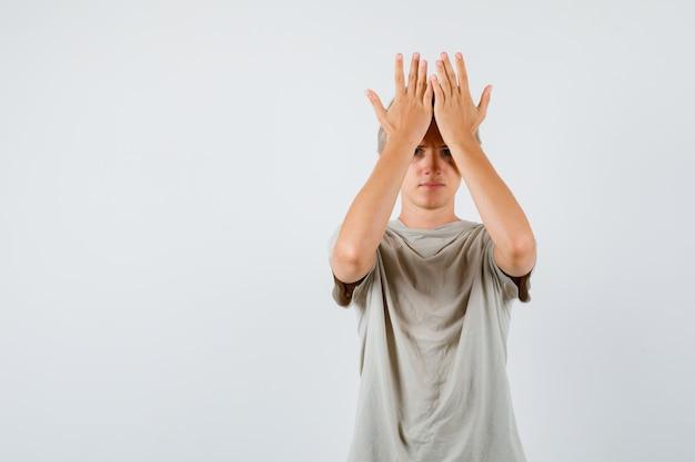 Молодой подросток мальчик держит руки на лбу в футболке и выглядит нервным, вид спереди.