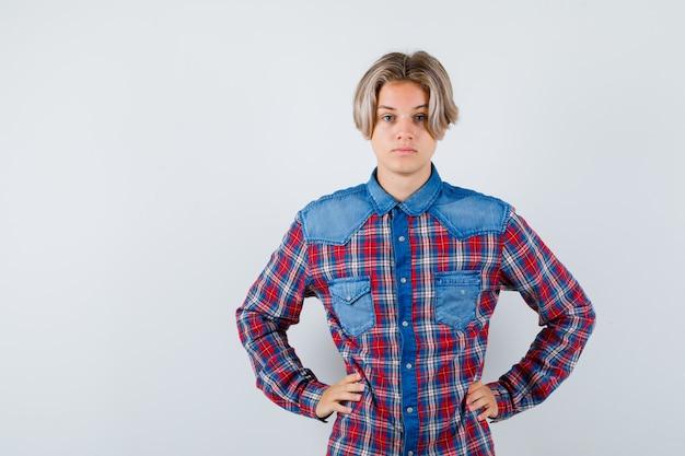 チェックのシャツを着て腰に手を保ち、真剣に見える若い十代の少年、正面図。