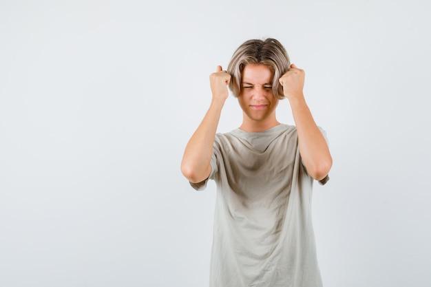 若い十代の少年は、tシャツを着て頭の近くで上げられた握りこぶしを保ち、忘れているように見えます。正面図。