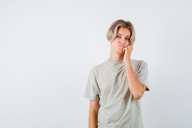 Tシャツを着て頬をもたれ、がっかりしているように見える若い10代の少年。正面図。
