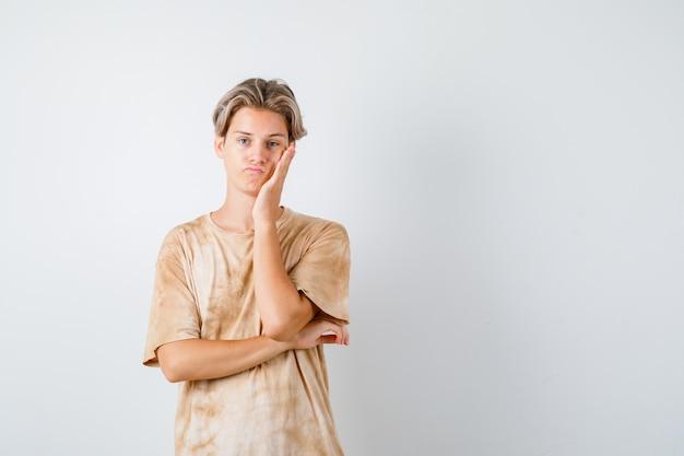 Tシャツを着て手のひらに頬をもたれ、失望した、正面図を見て若い10代の少年。