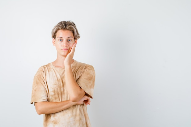 Giovane ragazzo adolescente che si appoggia guancia sul palmo in maglietta e sembra deluso, vista frontale.