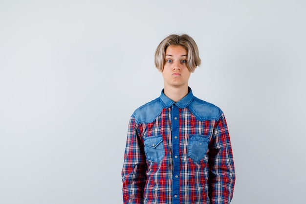 Young teen boy looking at camera in checked shirt and looking bewildered. front view.