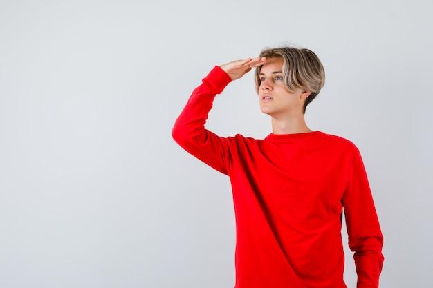 Молодой мальчик-подросток смотрит далеко с рукой над головой в красном свитере и смотрит сосредоточенно, вид спереди.