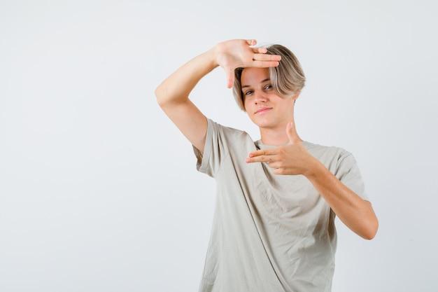 若い十代の少年は、tシャツの指銃でフレームジェスチャーを作成し、自信を持って見えます。正面図。