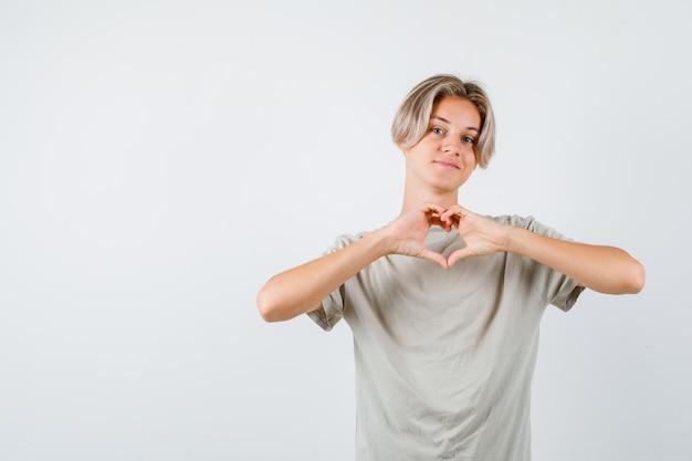 Giovane ragazzo adolescente che fa a forma di cuore con le mani in maglietta e sembra allegro. vista frontale.