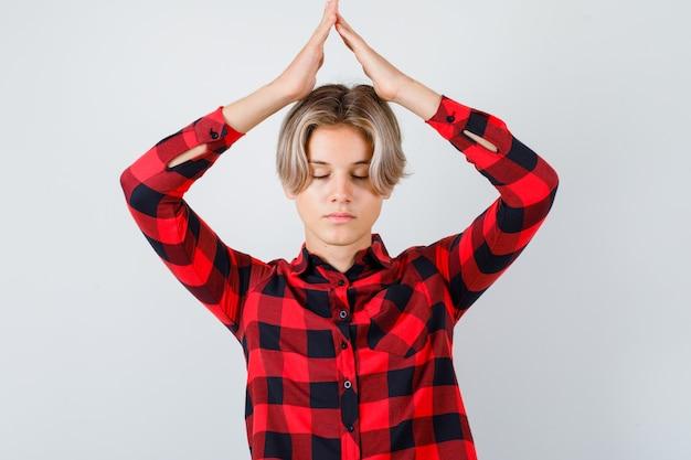 チェックのシャツを着て頭上で家の屋根のジェスチャーをし、平和な正面図を探している若い十代の少年。