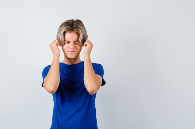 파란색 티셔츠에 손가락으로 귀를 막고 겁을 먹고 있는 어린 10대 소년.