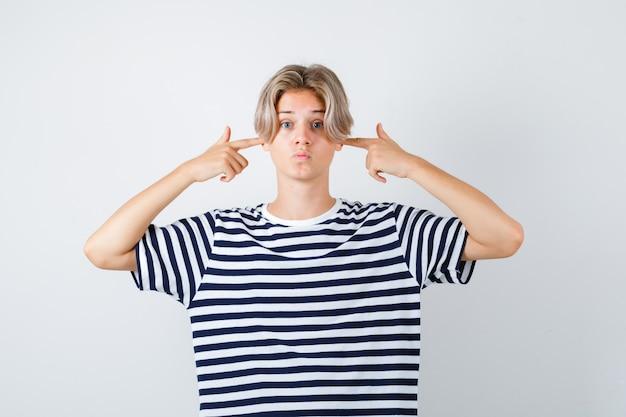 若い十代の少年は指で耳を塞ぎ、縞模様のtシャツに唇をふくれっ面し、怖がっています。正面図。
