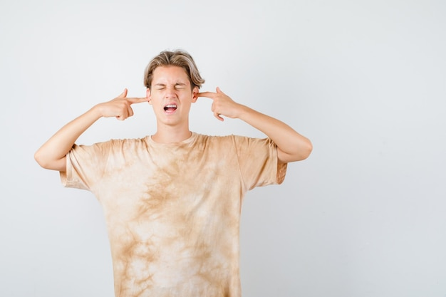 Giovane ragazzo teenager che tappa le orecchie con le dita in maglietta e sembra infastidito. vista frontale.