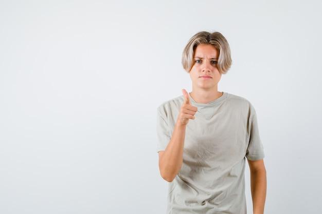 Tシャツを着てカメラを指差してがっかりしている若い10代の少年。正面図。