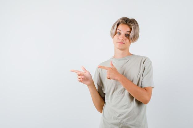 Молодой подросток мальчик указывая налево в футболке и выглядя невежественным. передний план. Premium Фотографии