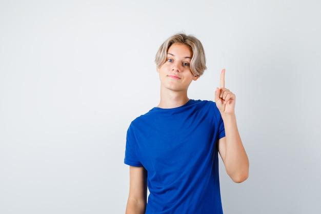 파란색 티셔츠를 입고 자신감을 보이는 어린 10대 소년.