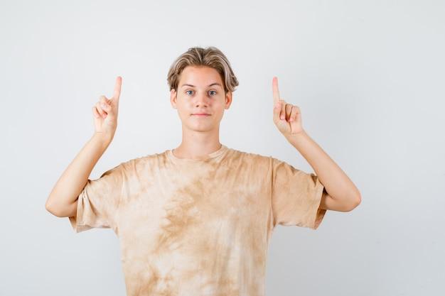 Молодой мальчик-подросток, указывая вверх в футболке и выглядел уверенно. передний план.