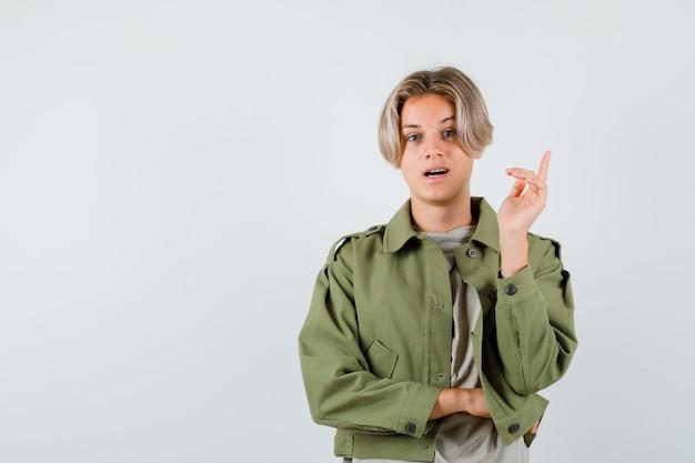 Giovane ragazzo adolescente che indica in su in t-shirt