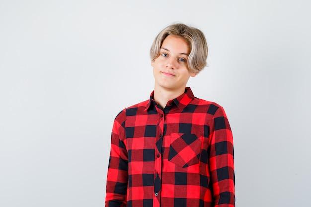 Giovane ragazzo adolescente in posa mentre in piedi in camicia a quadri e guardando fiducioso, vista frontale.