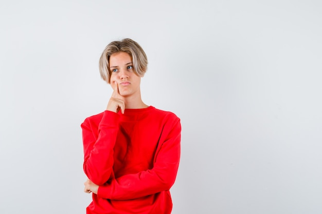 어린 십대 소년이 뺨에 손가락을 대고 빨간 스웨터를 입고 슬픈 앞모습을 보고 있습니다.
