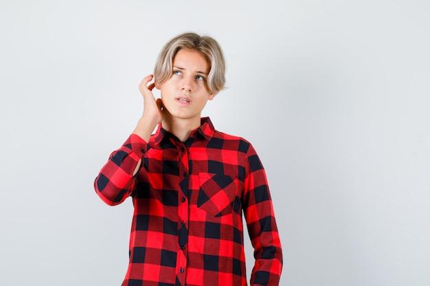チェックのシャツで頭をかいて、夢中になっている、正面図を探している若い十代の少年。
